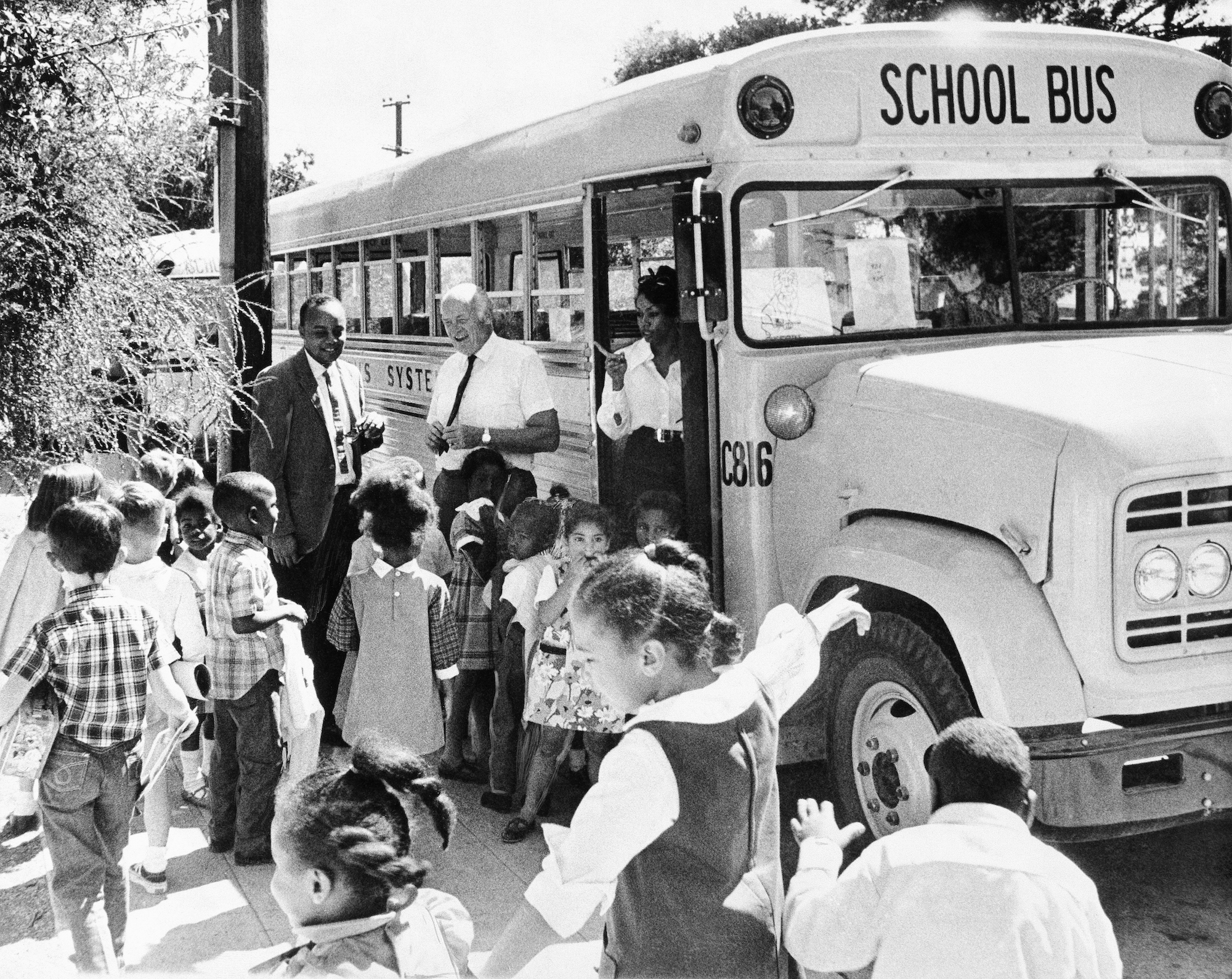 A black and white photo of Black children heading for a school bus while adults supervise